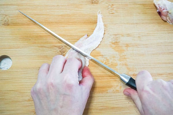 hands cutting chicken wings on a wooden cutting board
