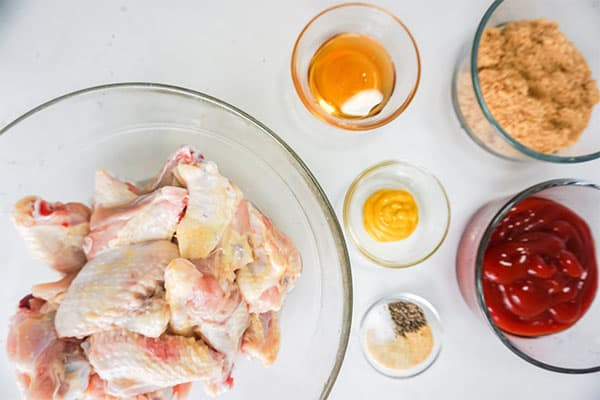 glass bowls of raw chicken wings, honey, brown sugar, ketchup, mustard and seasonings on a white background