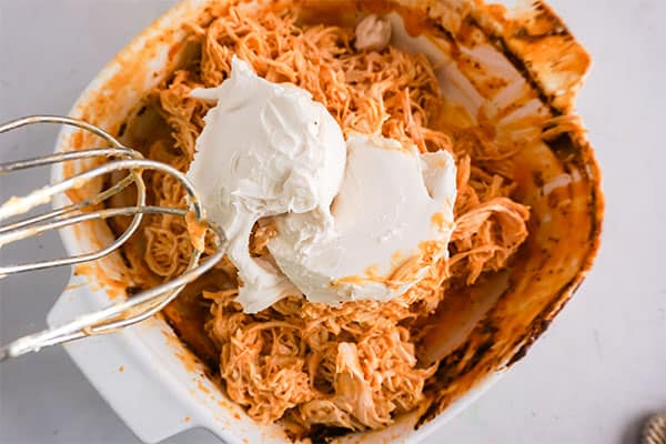 beating together the ingredients for baked buffalo chicken dip in a white dish