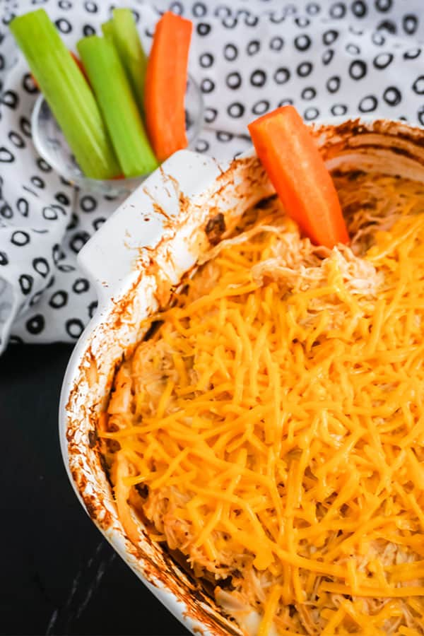 Baked Buffalo Chicken Dip in a white dish next to carrot and celery sticks and a white cloth with black circles on it