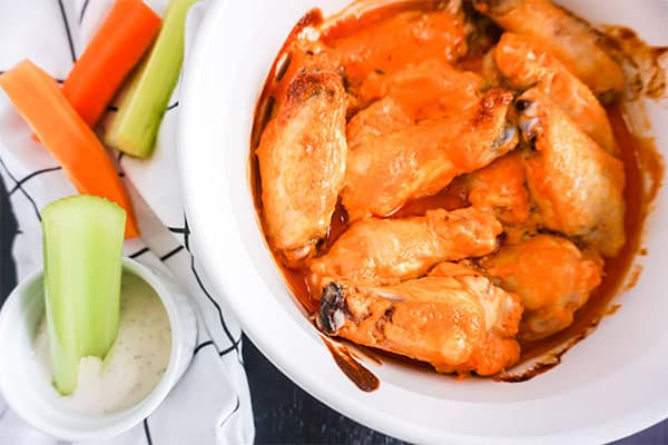 overhead view of Baked Buffalo Chicken Wings in a white dish next to celery in a dip with more carrots and celery on a white cloth in the background