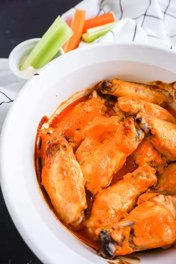 Baked Buffalo Chicken Wings in a white dish next to celery in a dip with more carrots and celery on a white cloth in the background