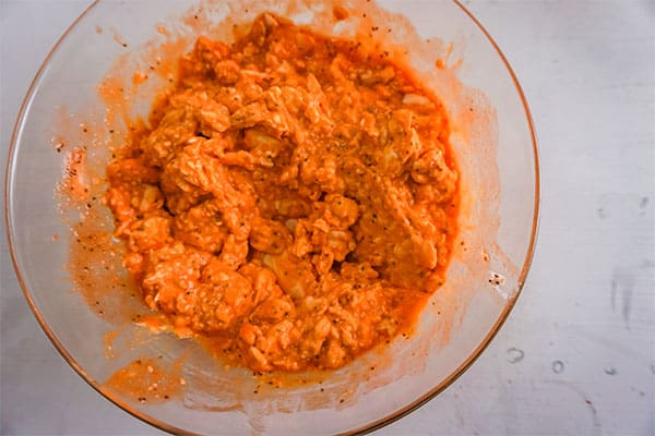 buffalo chicken dip in a glass bowl on a white background