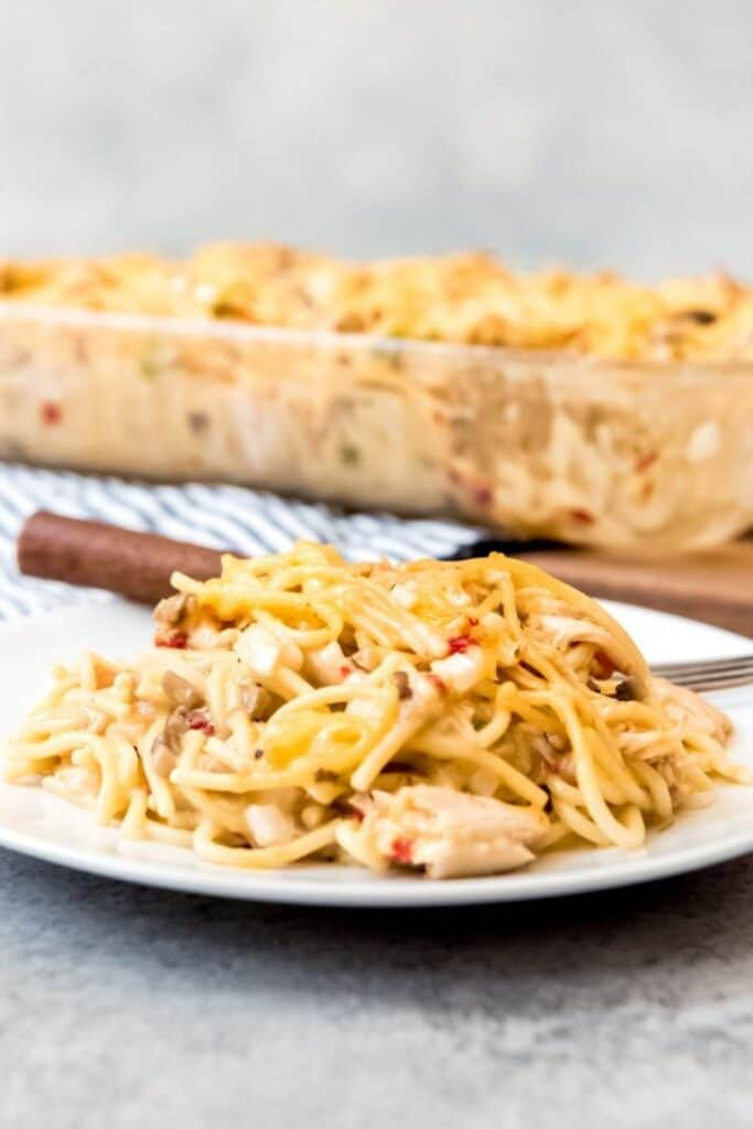 chicken spaghetti casserole on a white plate next to a fork with more casserole in a glass dish in the background