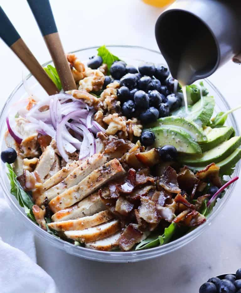 dressing being poured on grilled chicken salad with bacon and avocado in a glass bowl on a white background