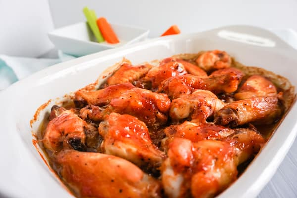 Baked BBQ Chicken Wings in a white dish next to carrot and celery sticks in sauce