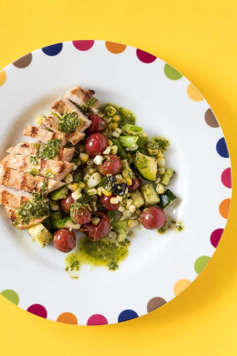 lime grilled chicken with vegetables and herb sauce on a white plate with colored dots on it on a yellow background