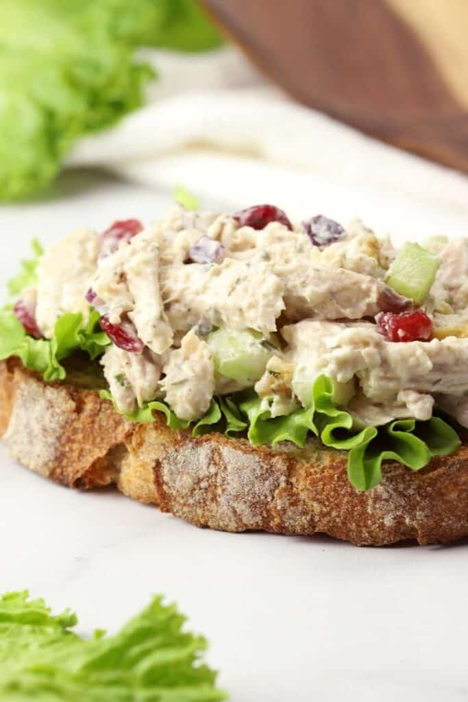 rotisserie chicken salad on a slice of bread on a white background