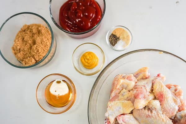 brown sugar, ketchup, honey, mustard, seasonings, raw chicken wings in glass bowls on a white background