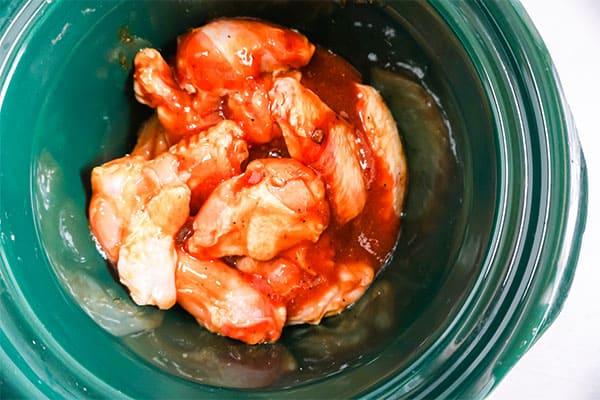 bbq chicken wings in a green slow cooker