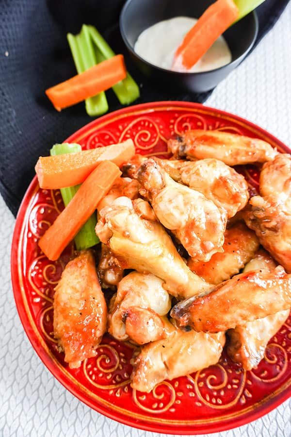 overhead view of Slow Cooker BBQ Chicken Wings next to carrots and celery on a red plate with more carrots and celery in a black bowl next to a black cloth in the background