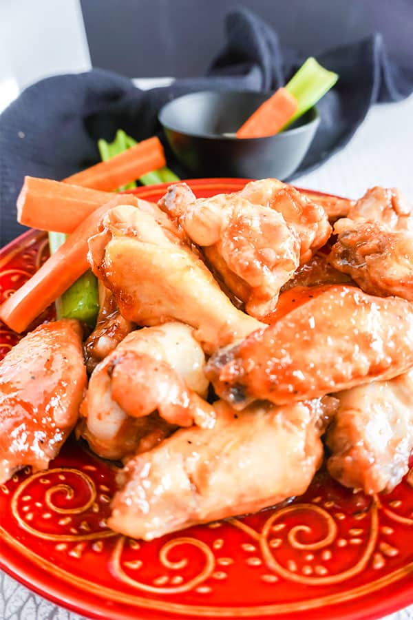 Slow Cooker BBQ Chicken Wings next to carrots and celery on a red plate with more carrots and celery in a black bowl next to a black cloth in the background
