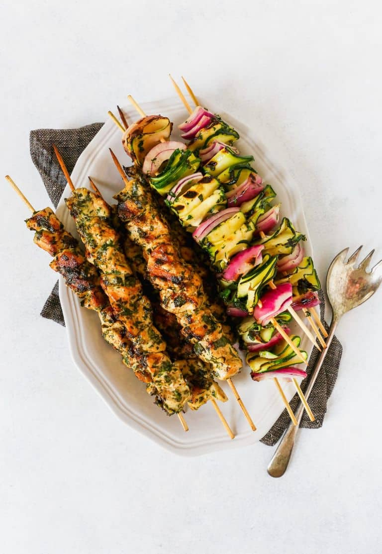 triple herb chicken and zucchini skewers on a white plate next to a fork on a white background