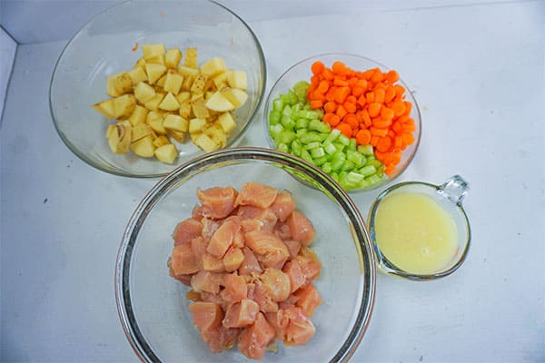 cubed raw chicken, diced potatoes, chopped celery and carrots, and broth in glass bowls on a white background