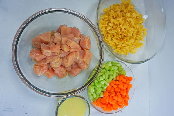 cubed raw chicken breast, noodles, chopped carrots and celery, and broth in glass bowls on a white background