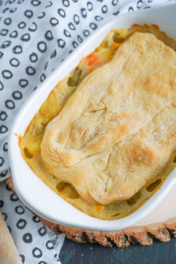Homestyle Chicken Pot Pie in a white baking dish next to a white cloth with gray circles on it