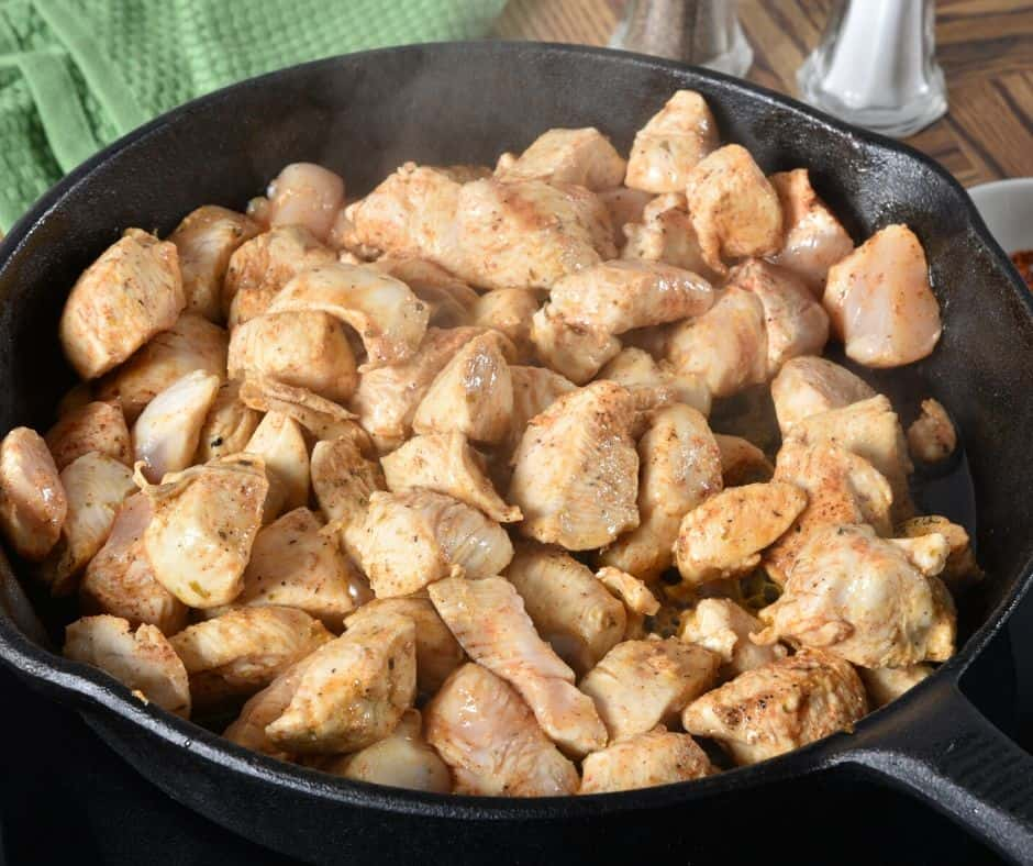 cut up chicken breasts being sauteed in a skillet
