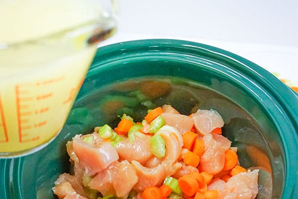 broth in a glass measuring cup above chicken, celery, carrot, spices in a green slow cooker