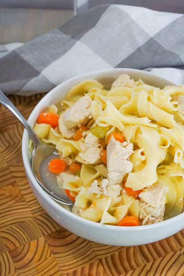 Slow Cooker Chicken Noodle Soup in a white bowl with a spoon in it on a brown table next to a gray and white checkered cloth