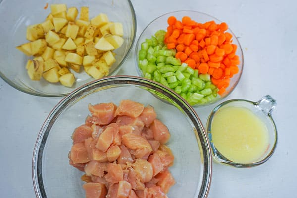 diced potatoes, cut up carrots and celery, chicken broth, and cut up raw chicken in glass bowls on a white background