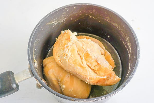 cooked chicken breasts in a pot on a white background
