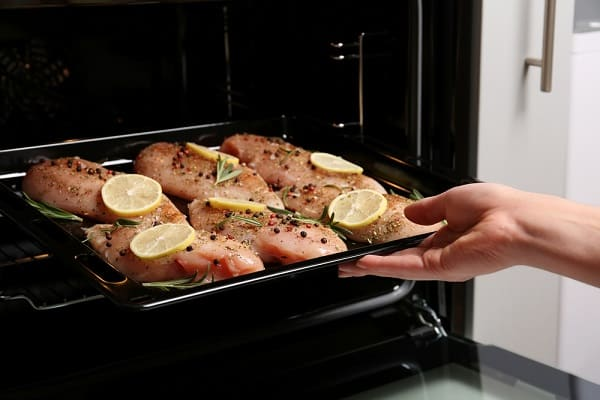 chicken breasts with lemon slices on them on a baking pan being placed in an oven