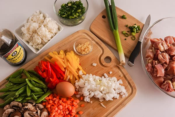 all of the ingredients needed to make chicken fried rice, the vegetables are on cutting boards, rice is in a white bowl, chicken is in a glass bowl, soy sauce is in a bottle