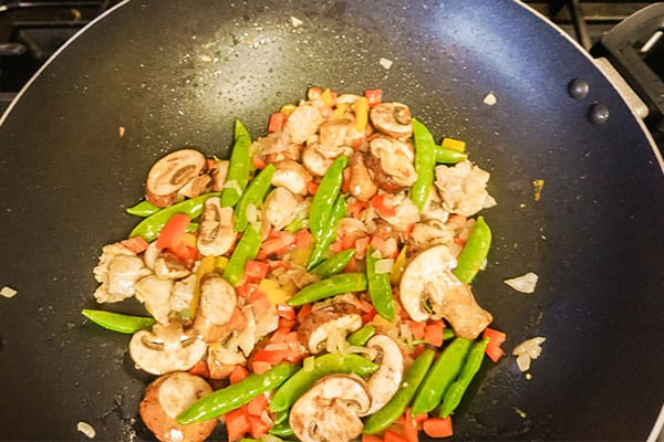 oil, chicken, onion, peppers, carrots, mushrooms, diced tomato, snow pea pods, egg and garlic cooking in a skillet
