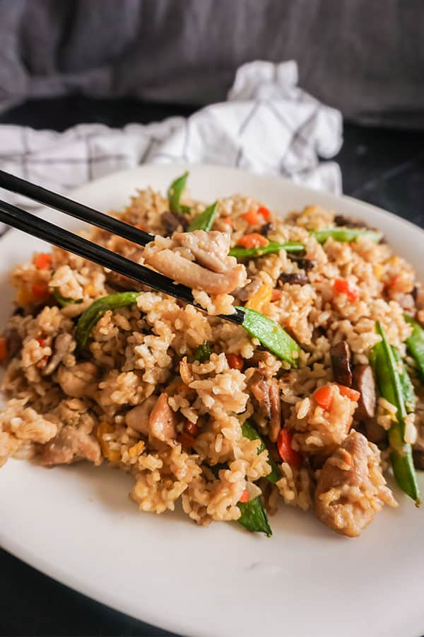 black chopsticks holding some chicken fried rice above chicken fried rice on a white plate on a brown table