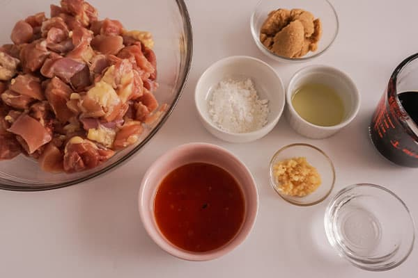 glass and ceramic bowls of diced raw chicken, red chili sauce, rice wine vinegar, soy sauce, brown sugar, cornstarch, minced garlic on a white background