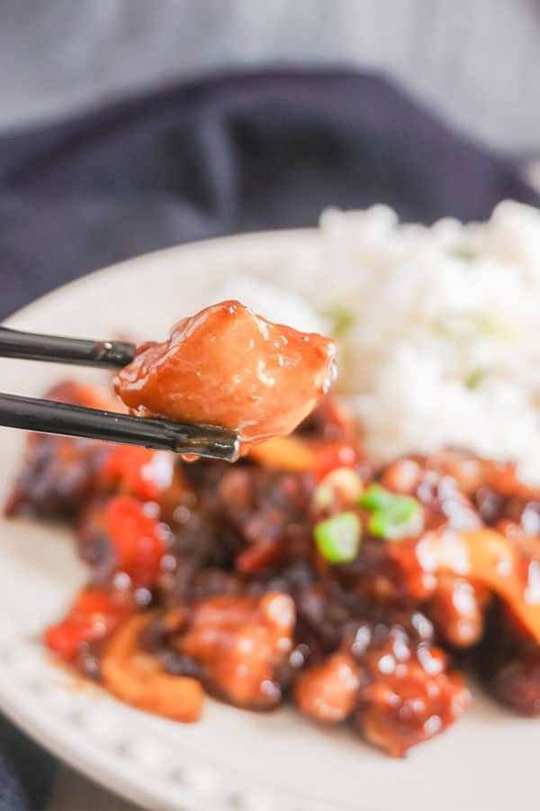 black chopsticks holding a piece of Spicy General Tso's Chicken above a plate of more of the chicken and rice