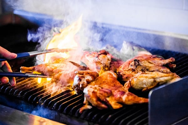 a person using tongs to turn over a chicken on the grill as it causes flames in the grill