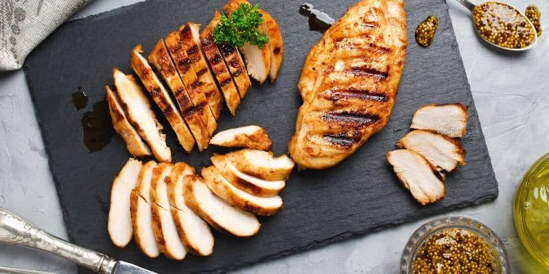sliced grilled chicken on a cutting board