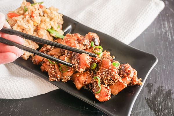 Take-Out Style Sesame Chicken on a black plate next to brown rice with chopsticks on the plate, on a white cloth on a brown table