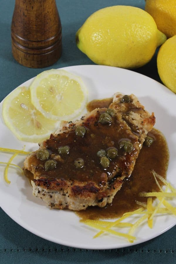 Lemon Chicken Piccata  next to lemon slices and lemon zest on a white plate on a dark blue cloth next to some lemons and a salt or pepper shaker