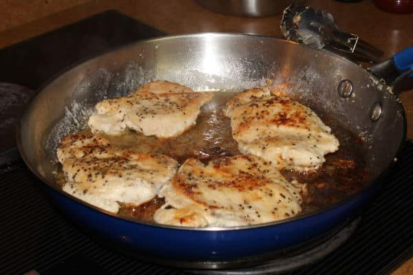 chicken breasts cooking in a skillet