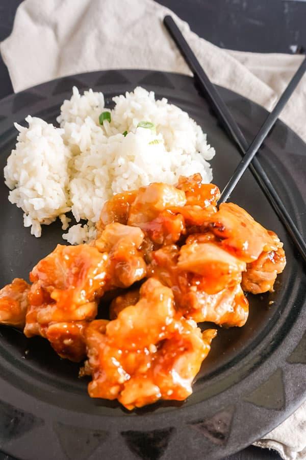 orange chicken above more orange chicken and white rice next to black chopsticks on a black plate