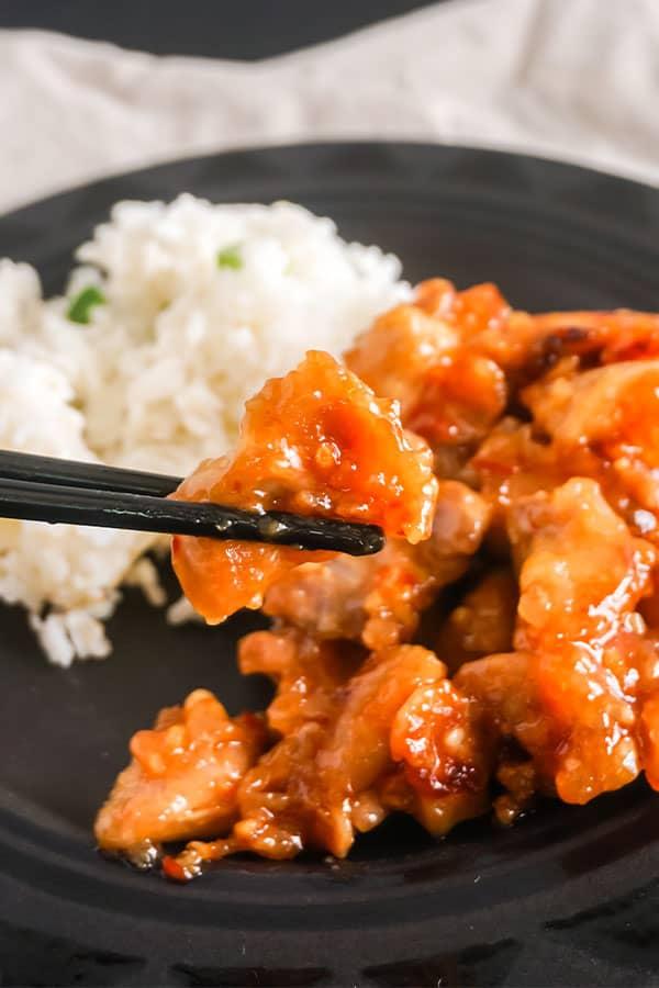 black chopsticks holding a piece of orange chicken above more orange chicken and white rice on a black plate