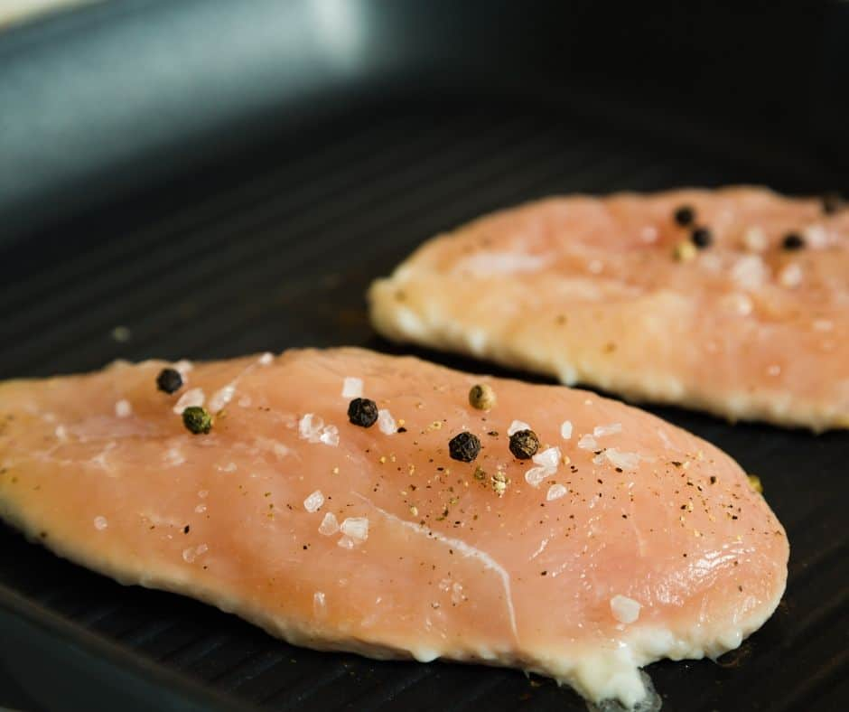 chicken breasts being cooked by the pan-fry method