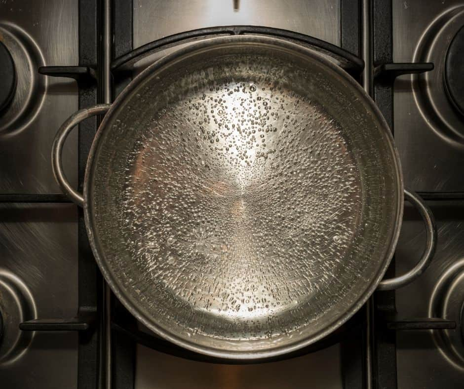 overhead view of water simmering in a pot on the stove