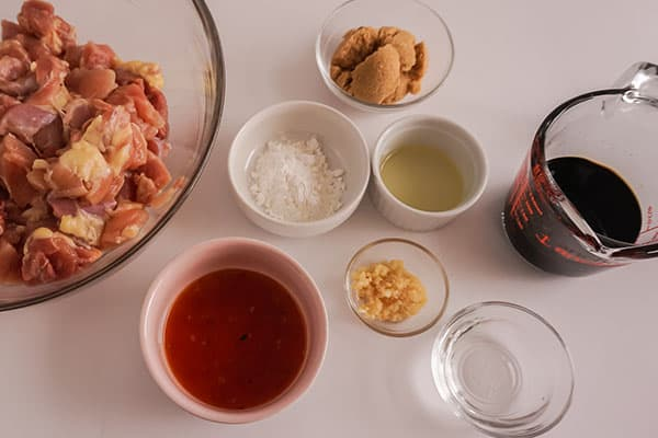 ingredients in glass bowls and white bowls needed to make Slow Cooker General Tso's Chicken