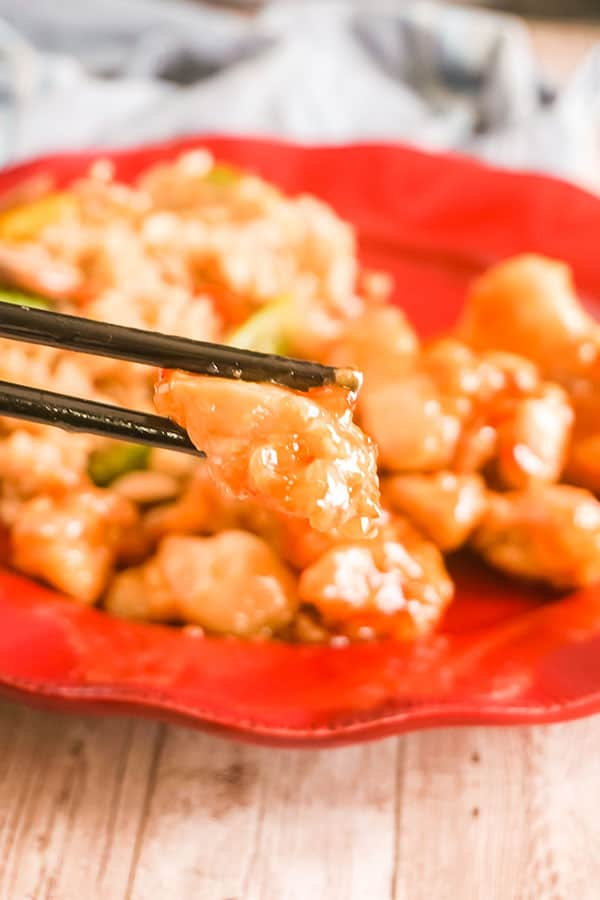 closeup of Slow Cooker Orange Chicken and rice on a red plate with black chopsticks on it