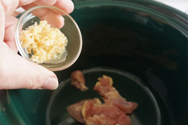 minced garlic being added to chicken in a slow cooker
