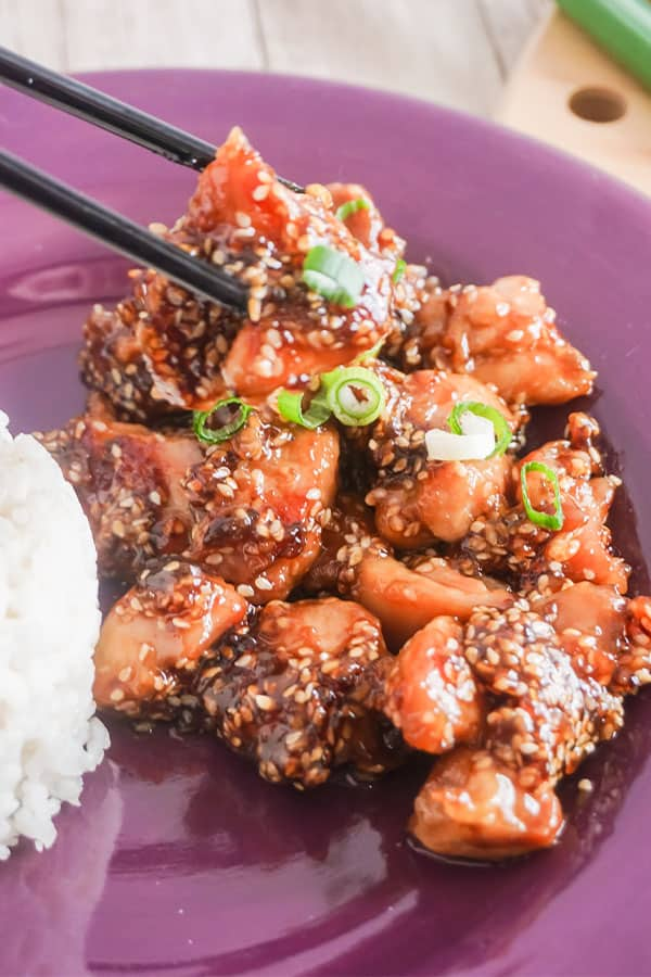 chopsticks holding some Slow Cooker Sesame Chicken next to white rice on a purple plate