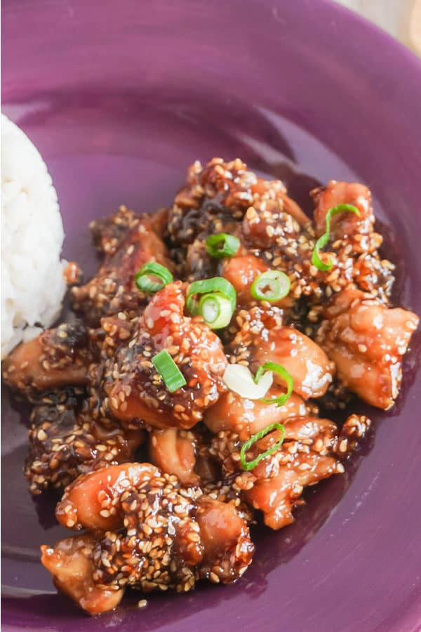 Slow Cooker Sesame Chicken next to white rice on a purple plate