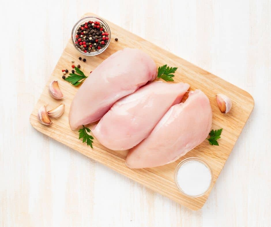 three raw chicken breasts next to garlic and other ingredients on a wooden cutting board