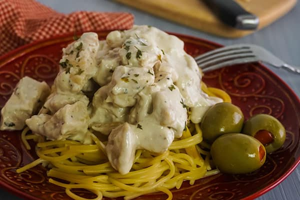 Homemade Chicken Alfredo next to olives and a fork on a red plate