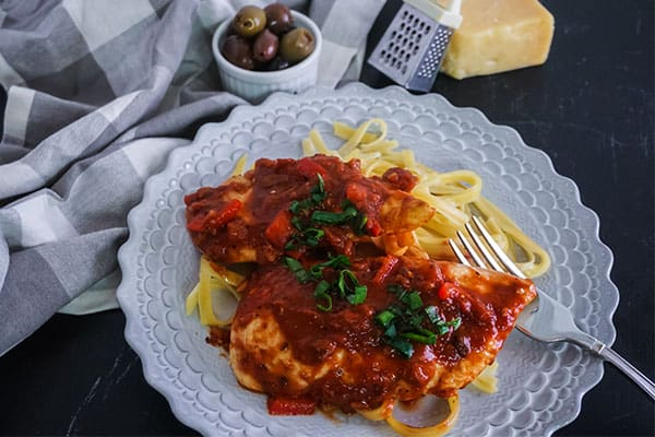 Homemade Chicken Cacciatore next to a fork on a white plate on a table next to a gray and white checkered cloth, a bowl of olives, a mini cheese grater, and a block of cheese