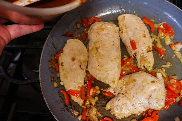 olive oil, chicken red pepper, garlic and onion cooking in a skillet