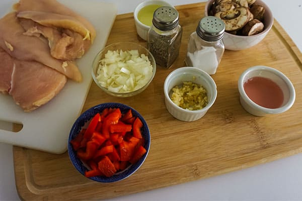 raw chicken breasts on a white cutting board, bowls of diced onion, white wine, garlic, stewed tomatoes and mushrooms, next to salt and pepper shakers on a wooden cutting board